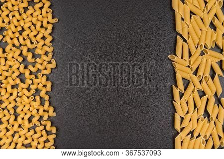 Cavatappi And Penne On Gray Background. Ingredients Of Italian Cuisine. Food Background.