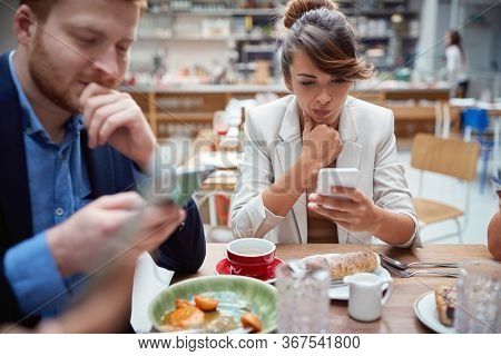 business people  at lunch, not talking, worried, after covid, distracted from each other by cell phones. not present, social issues, recessions, problems.