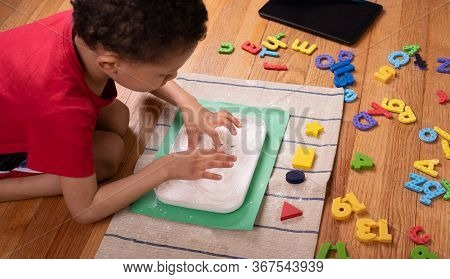 Tablet, \ncolored Letters ,kid Drawing With  Flour On Floor.\npreschool Boy,\nhome School Concept,
