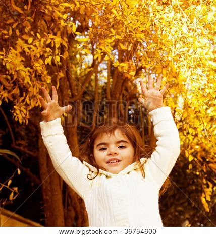 Photo of sweet small girl jumping in autumn forest, lovely female child playing on backyard, adorable little kid in warm sweater with raised hands having fun in fall woods, happy childhood concept