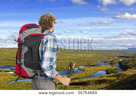 Hiker looking into the distance, upstream a small river, shielding his eyes and holding two walking sticks