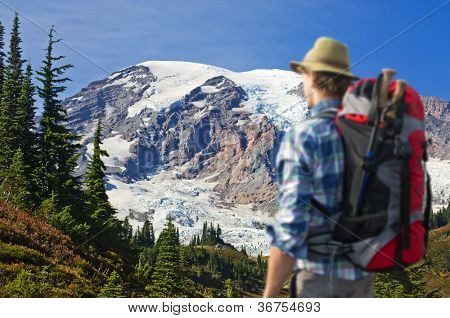Hiker absorbing the magnificent view of Mount rainier. The hiker is out of focus, the view on the mountain is christal clear.