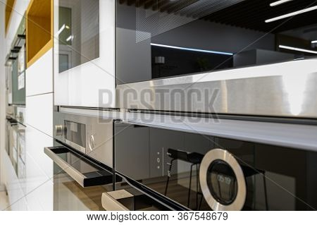 Rows of brand new modern electric ovens in home appliance retail store showroom