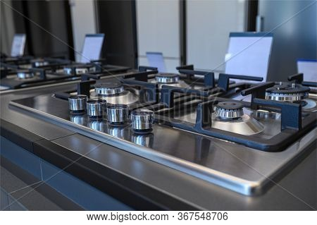 Rows of brand new gas stoves and ovens with stainless steel trays in appliance retail store