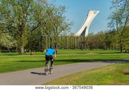 Montreal, Ca - 22 May 2020: Man Riding A Bike In Parc Maisonneuve During Covid 19 Pandemic. Olympic