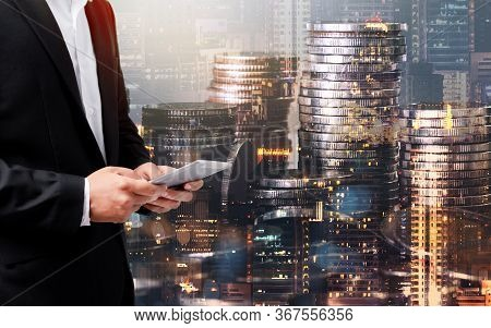 Double Exposure Of Success Businessmanusing Tablet Analyzing Data On Coin And City Background.time F