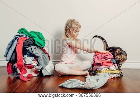 Mommy Little Helper. Cute Caucasian Girl Sorting Clothes. Adorable Funny Child Arranging Organazing