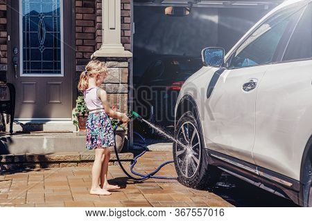 Young Preschool Girl Washing Car On Driveway In Front House On Summer Day. Kids Home Errands Duty Ch