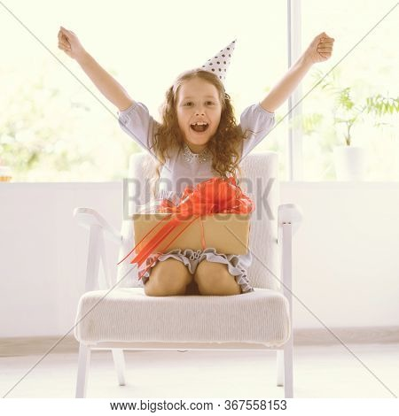 Happy Delighted Little Girl Sitting At Home On The Armchair On Her Birthday. The Festive Cap Is Dres