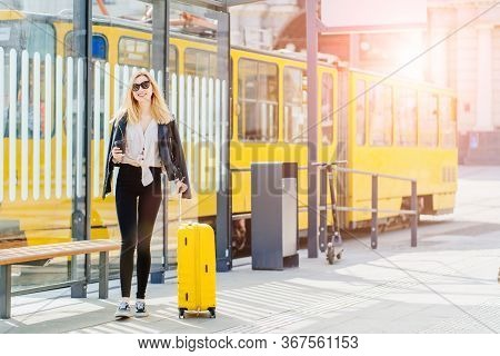 Young Blonde Woman Traveler Millennial On Bus Or Tram Stop
