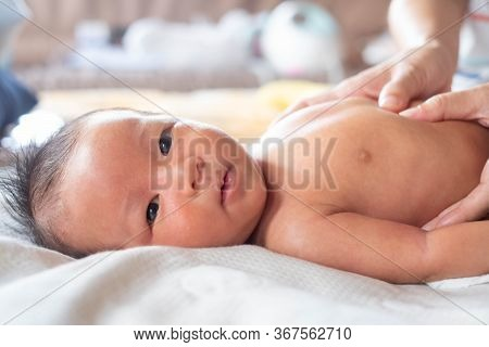 Close-up Hands Of Mother Touching And Take Care Newborn Infant  Baby With Gas Pain In The Stomach Or
