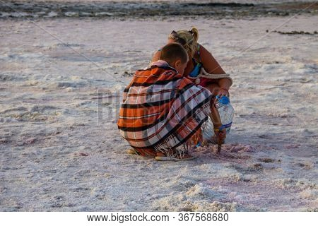 Genichesk, Ukraine - August 23, 2017: People Gathering Salt Of Pink Salty Siwash Lake, Colored By Mi