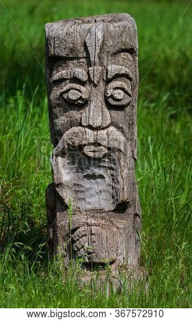 Wooden Idol On The Background Of Green Grass. Cossack Wooden Statue