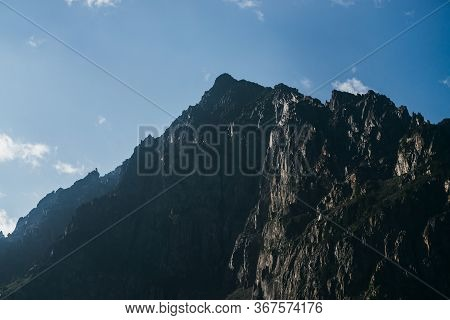 Awesome View To Pointy Peak Of Dark Rock In Clear Blue Sky. Minimalist Alpine Landscape With Big Bla