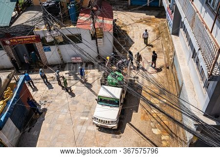 A Team Of Workers Spraying Houses Walls And Sidewalks With A Disinfectant Chlorine Compound In An At