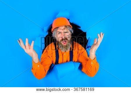 Through Paper. Bearded Builder Look Through Paper. Confused Worker In Helmet. Repair. Bearded Man. T