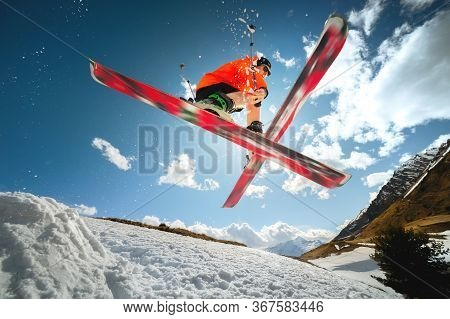 A Young Athlete Skier Does A Trick On A Snow Kicker Jump And Cross Skis In A Counter Light Against A