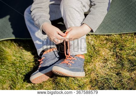 Child Trying To Tie Shoelaces On Shoes. Close Up, Pulls Lace. Sitting On A Green Lawn. Bright Colour