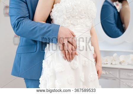 Newly Married Couple Holding Hands With Woman's Hand On Top Of Man's Hand. Wedding