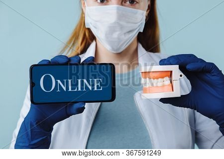 Portrait Of Beautiful Female Dentist Posing In Dental Clinic Holding Smartphone With Green Screen An