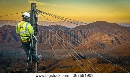 Lineman (or Lineworker Or Engineer) In A Remote Desert Landscape Fixing A Telephone Line