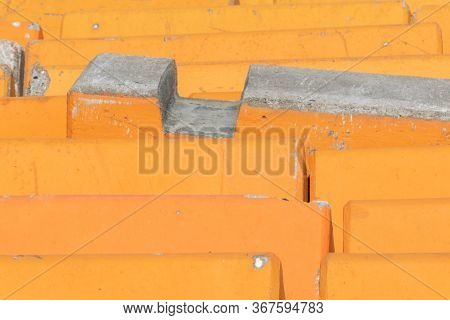 Close Up Detail Of Orange Concrete Road Barriers Used To Line Streets Protecting Pedestrians From Te