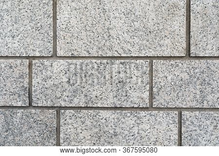 Background Texture Of A Grey Granite Rectangular Brick Wall With Neat Grouting In A Full Frame View