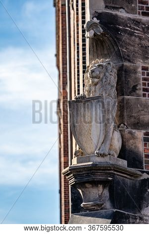 Heraldic Stone Carved Lion Statue With Shield On A Plinth On The Corner Of A Historic Brick Building