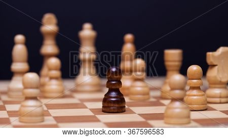 Chess, A Lot Of Chess Pieces On The Board. The White Pieces Surrounded The Black Pawn. A Stranger Su
