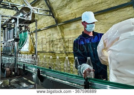 Pure Drinking Water Plant. Work Conveyor In The Enterprise. A Worker Places Liter Bottles On A Conve