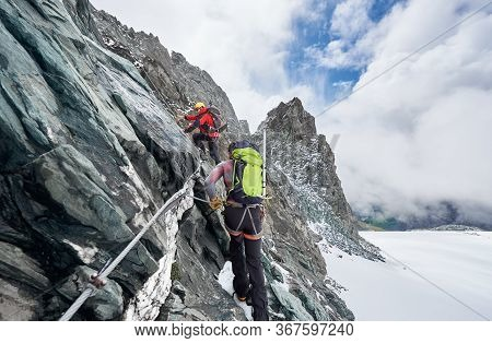 Back View Of Rock Climbers With Backpacks Using Fixed Rope While Ascending High Rocky Mountain. Male