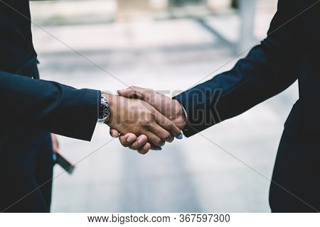 Colleagues In Suits Greeting Each Other.crop Business Coworkers In Strict Formal Black Suits With Wa
