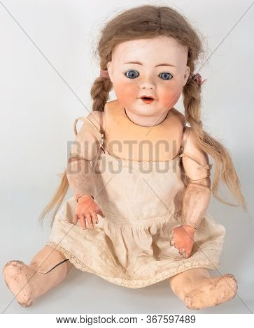 Frontal View Of Wooden Female Doll With Long Ponytail Hair And Blue Eyes While Wearing Light Brown D