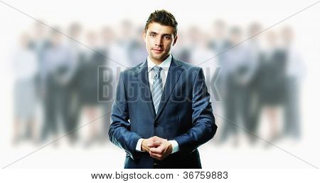 Creative image of attractive businessman in suit with crowd of people on background