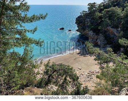 View From The Height Of A Wonderful Secluded Beach Among Mountains, Rocks, Sand, Sea Waves Constantl