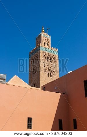 Minaret Of Koutoubia Mosque In Marrakesh, Morocco. Oriental Architecture Against Blue Sky. Travel Po