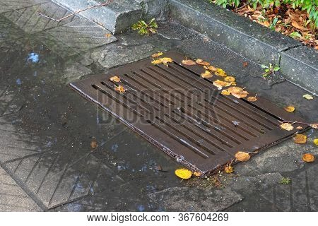 Old Storm Drain Or Storm Sewer On The Road In Rainy Day