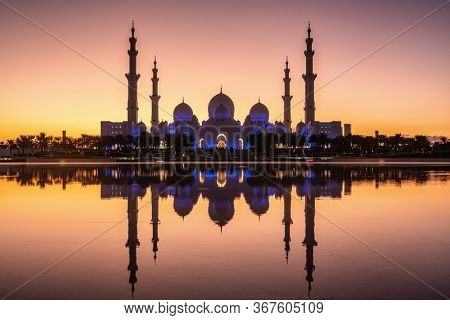 Grand Mosque at twilight in Abu Dhabi, UAE. Night illumination of the mosque with reflection in water
