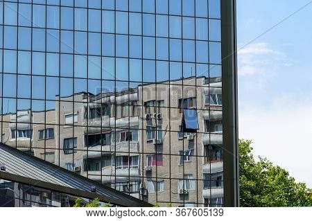 Old Residential Multi-storey Panel House Reflected In The Mirrored Wall Of An Office Building. Compa