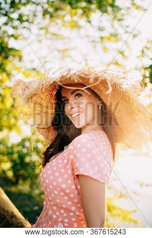 Beautiful Young Long-haired Brunette In Beach Straw Hat With Frayed Edges Wearing Pink Polka Dot Dre