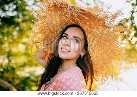 Beautiful Young Long-haired Brunette In Beach Straw Hat With Frayed Edges And Wearing Pink Polka Dot