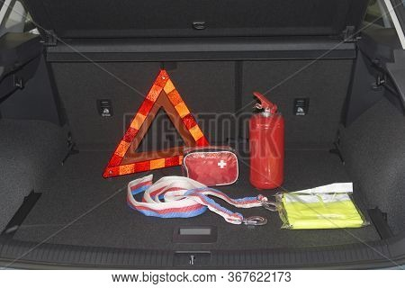 Travel Kit In The Trunk Of A Car. Fire Extinguisher, Tow Rope, Warning Triangle, Medical Kit, Reflec