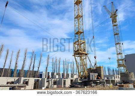 House Construction. Photos Of High-rise Construction Cranes And An Unfinished House Against A Blue S