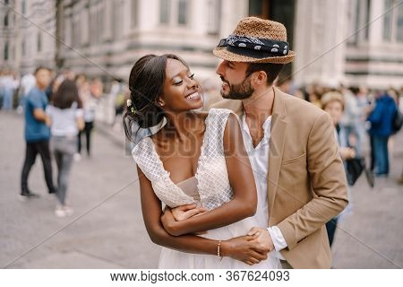 Multiracial Wedding Couple. Wedding In Florence, Italy. Caucasian Groom Hugs From Behind African-ame