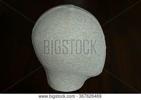 One Mannequin Head In Gray Matter On A Dark Brown Background