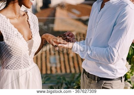 Multiracial Wedding Couple - African-american Bride And Caucasian Groom. Groom Puts A Ring On Brides
