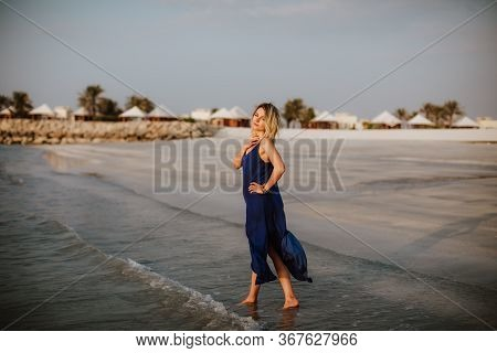 Young Blonde Woman In Dark Blue Sundress Walking Along The Coast With White Sand On A Background Of