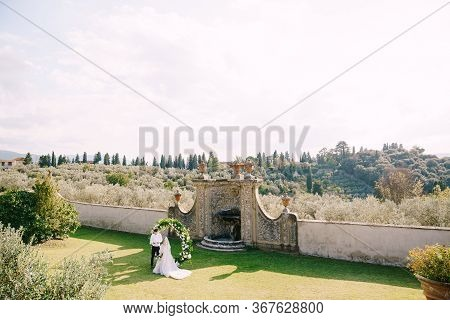 Wedding At An Old Winery Villa In Tuscany, Italy. Wedding Couple Under A Round Arch Of Flowers. The