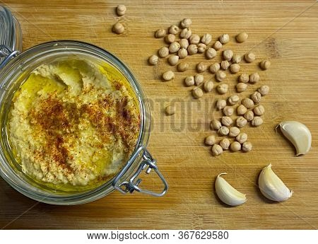 Homemade hummus in glass jar with chickpea beans and garlic cloves on wood background