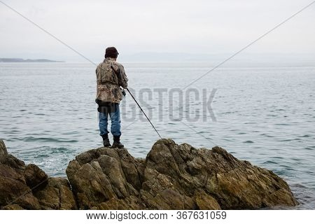 Fisherman catches fish on the rocks in the morning